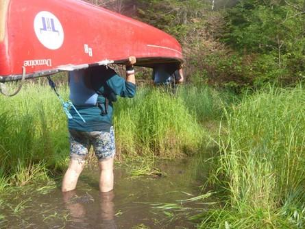 Campeur portant un canoë dans la boue.