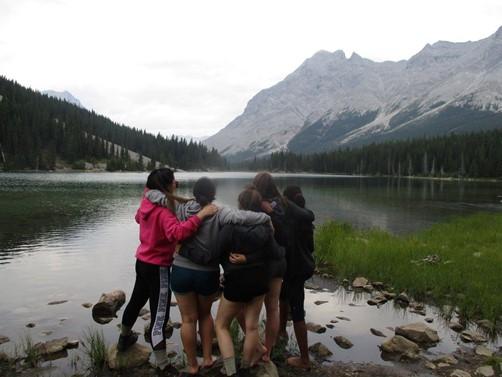 Des campeurs s'embrassant au bord de l'eau.
