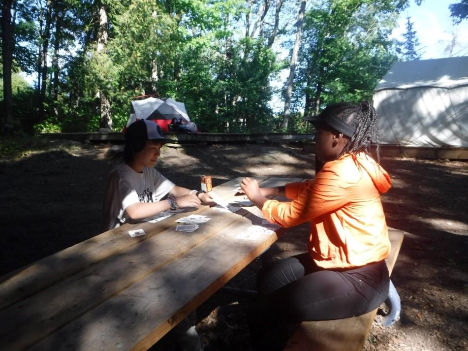 Conseiller et campeur jouant aux cartes au camping
